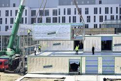 Ein 200-Tonnen-Kran montiert zurzeit 63 Raumzellen vor dem jetzigen Haupteingang des Universitätsklinikums Jena. Aus den von der Cadolto Thüringen GmbH vorgefertigten Elementen entsteht ein neues Bettenhaus. Foto: UKG / Grau